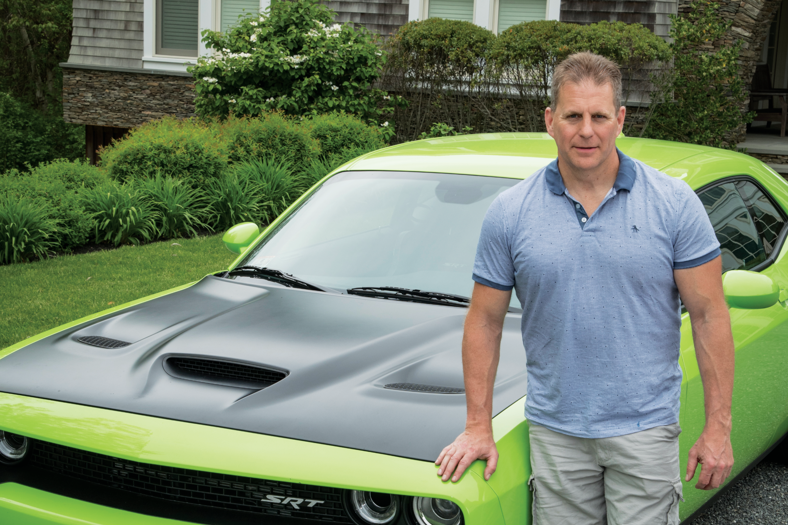 William Eigen standing in front of a green muscle car