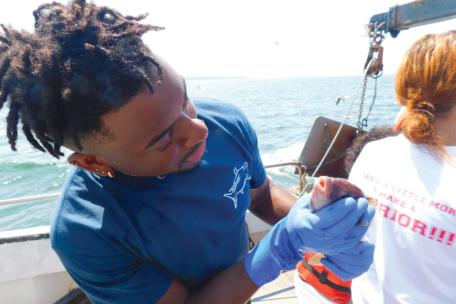 Gyasi Alexander inspects a fish on board a boat during URI's 2018 Summer Shark Camp for high school students.