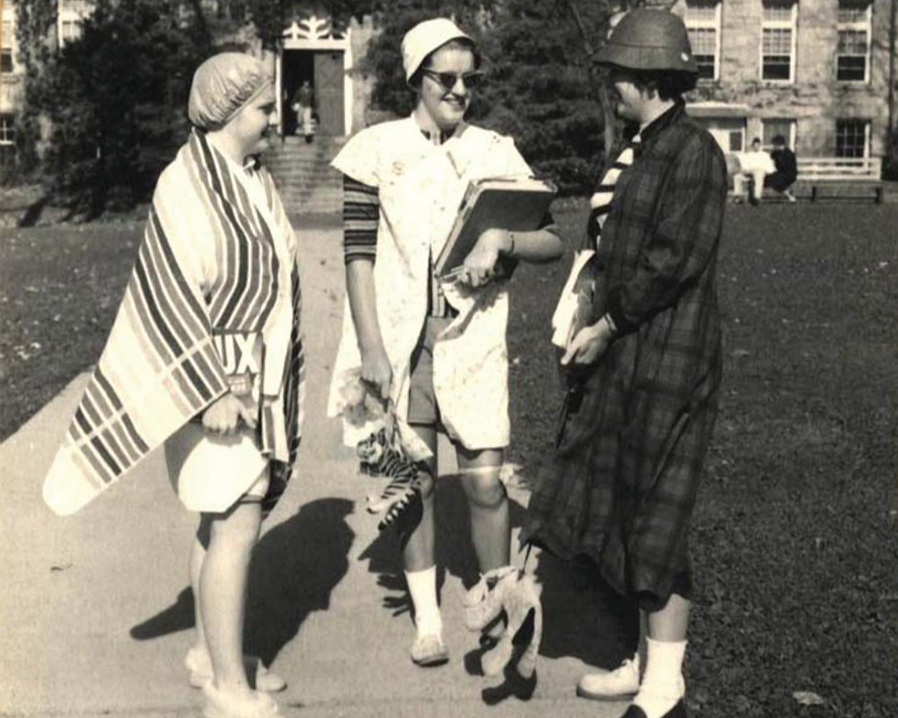 An old black and white taken in 1956 of three oddly dressed women on the URI Quadrangle
