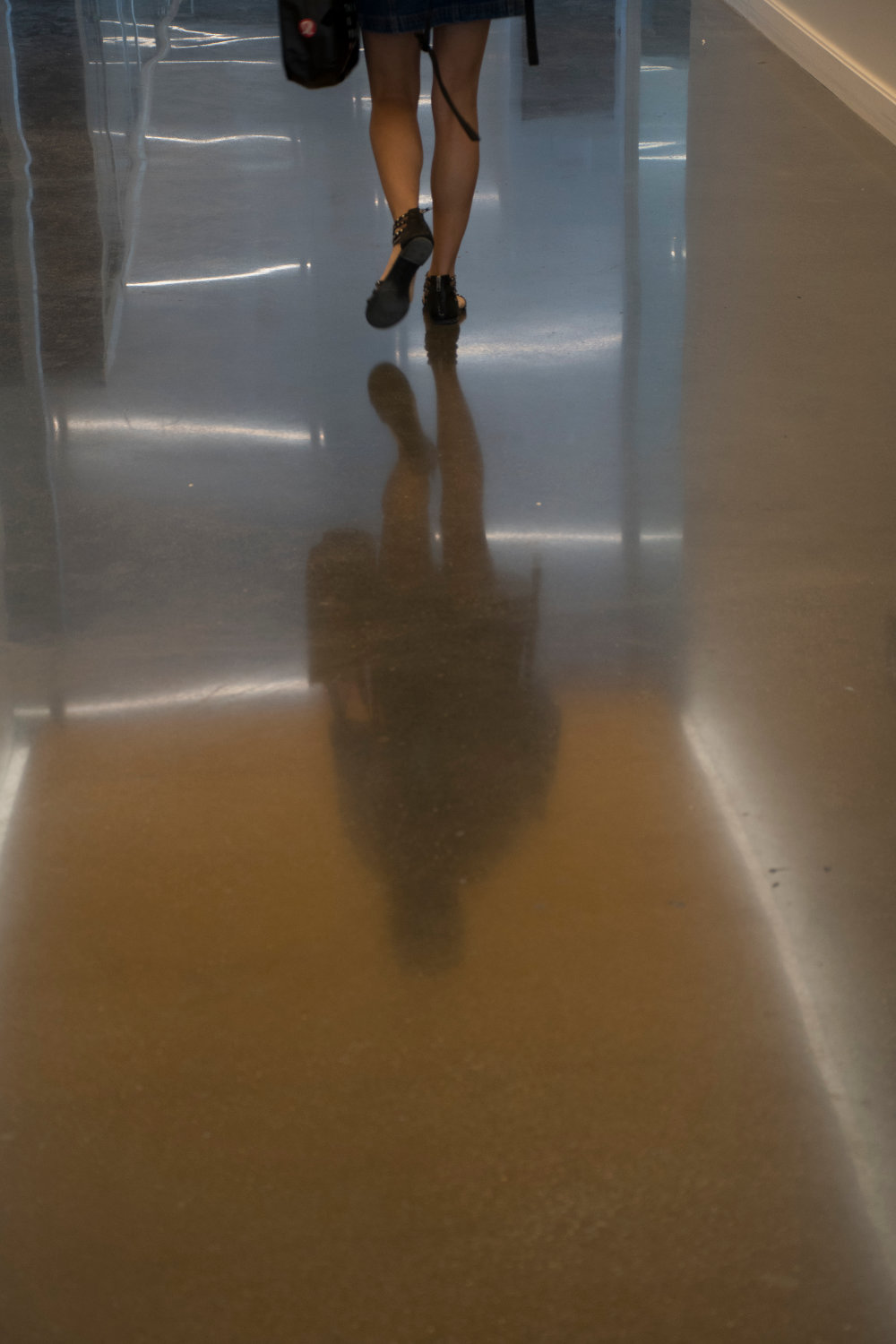 The smooth concrete hallway reflects the lights from the lighting above.