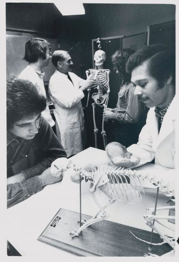 An old black and white photo of students and professors in a lab studying animal skeletons