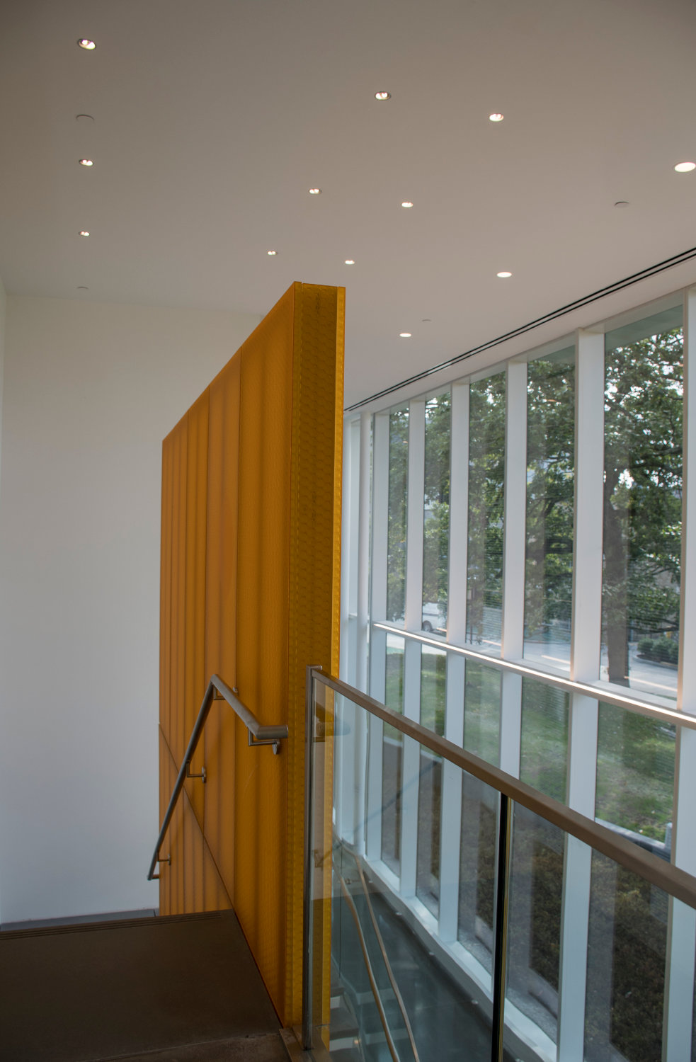 A staircase leads down to an open seating space on the ground floor level