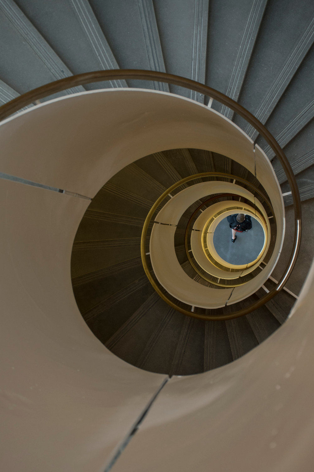 A view of a passerby walking beneath the center of the spiral staircase