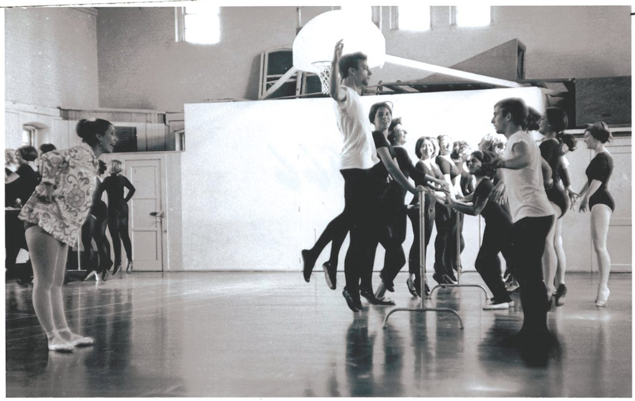An old black and white photo showing a ballet class held in a gymnasium