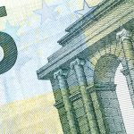 A close up view of printed European currency with architectural details and stars
