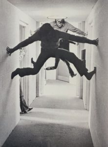 Students propping themselves above the floor in a corridor using their hands and feet agains the walls