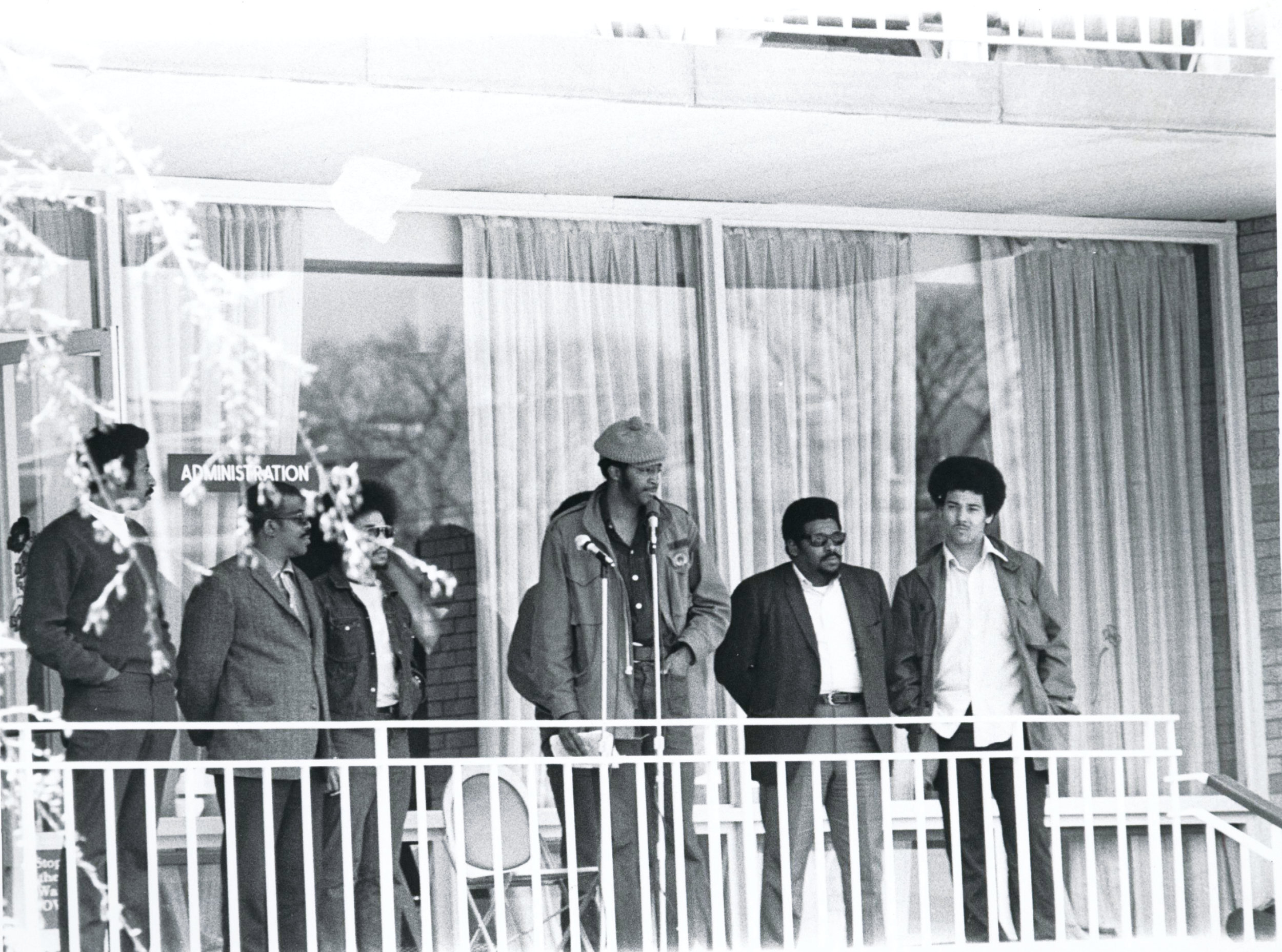 A group of Black student activists standing on the second floor balcony of the Carlotti Administrative Building