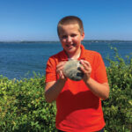 Cooper Monaco poses with the giant quahog he found last summer.