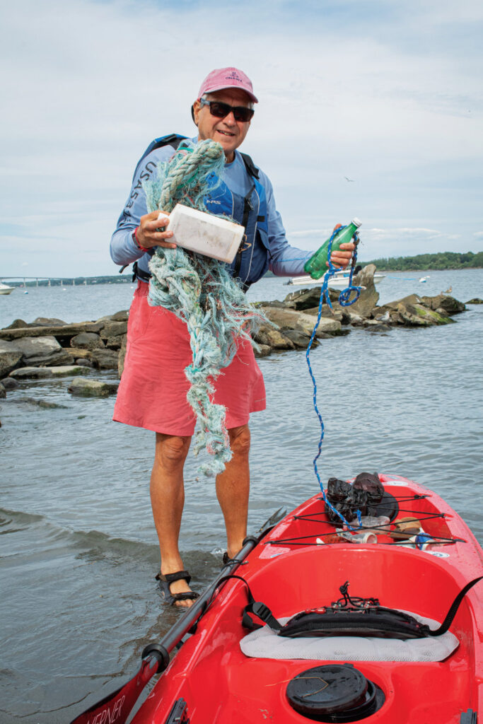 Dennis Nixon standing next to his kayak, holding up trash he finds in the bay.