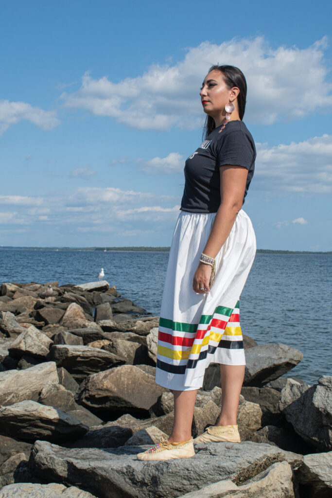 Leah Hopkins standing in profile on a rocky jetty next to Narragansett Bay