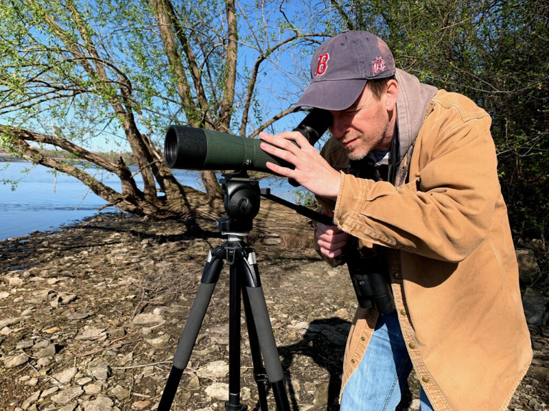 Andrew Forbes looking through a monocular on a tripod at the shore of a lake.