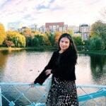 Lauren Machado, standing outdoors on a bridge overlooking water and buildings