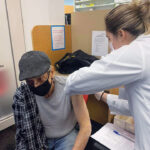 A seated client with their shirt rolled up, receiving a Covid vaccination