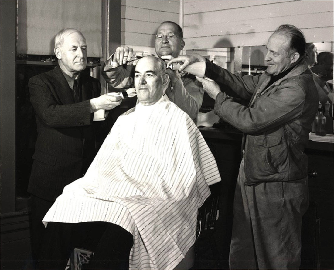 A historical black and white image of a person getting his hair clipped as two others look on.