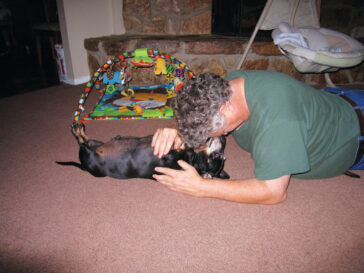 David A. Todd '74 playing on the floor with his dog Hunter, the inspiration behind the poem he submitted.