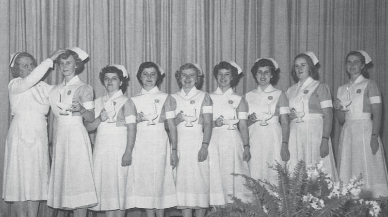 An old photo of a group of nurses standing in a line in uniform receiving degrees