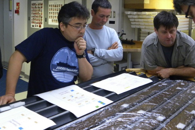 Yuki Morono (left) and Steven D'Hondt (far right) aboard the research drillship JOIDES Resolution with sediment cores gathered from the South Pacific Gyre. (Photo courtesy of IODP JRSO)