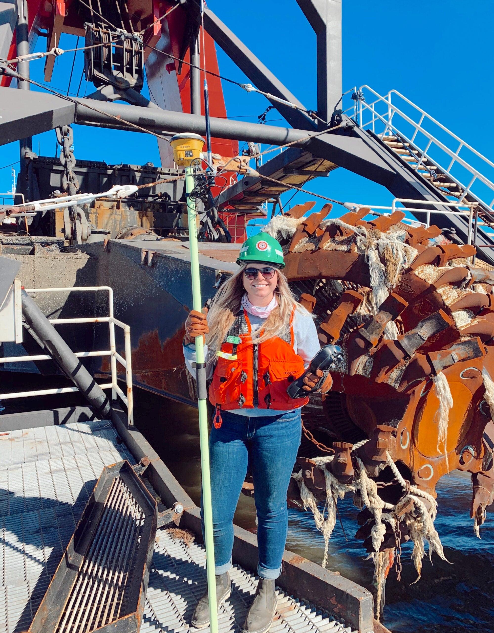 URI junior Faith Leonard holds survey equipment aboard a cutter dredge boat. Photo courtesy of Great Lakes Dredge & Dock Corporation