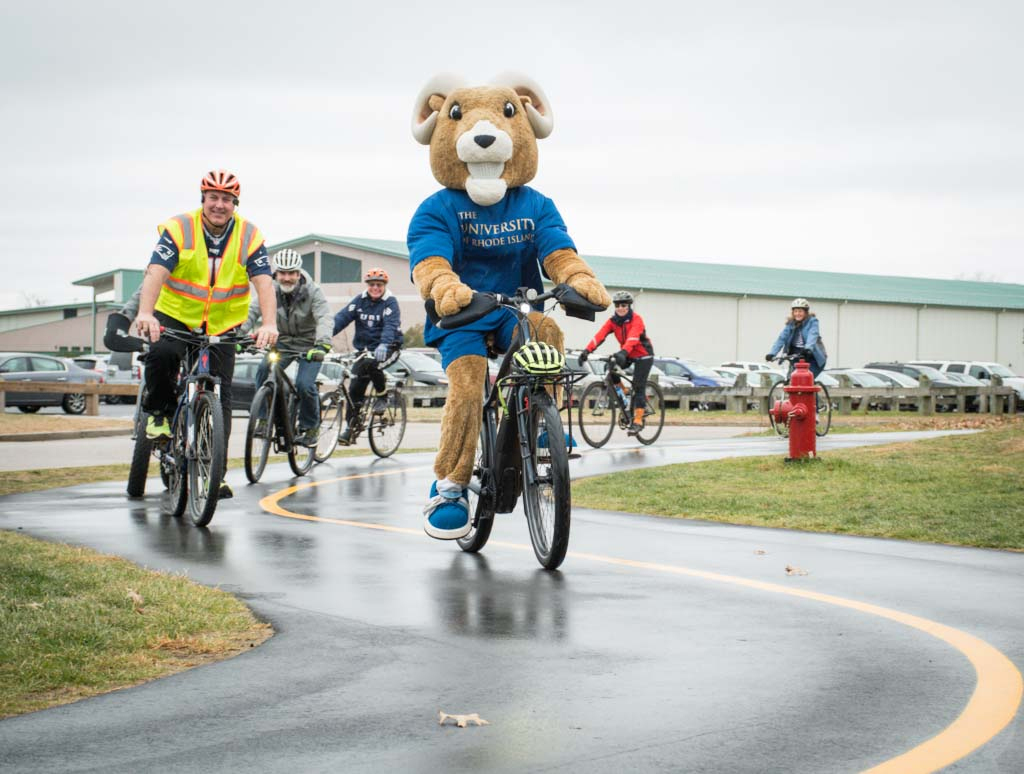 Rhody the Ram and Ken Ken Burke, assistant director of URI Capital Projects, celebrate the opening of the URI bike path