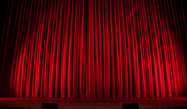 Picture of a stage with a red curtain. Photo by Rob Laughter on Unsplash.