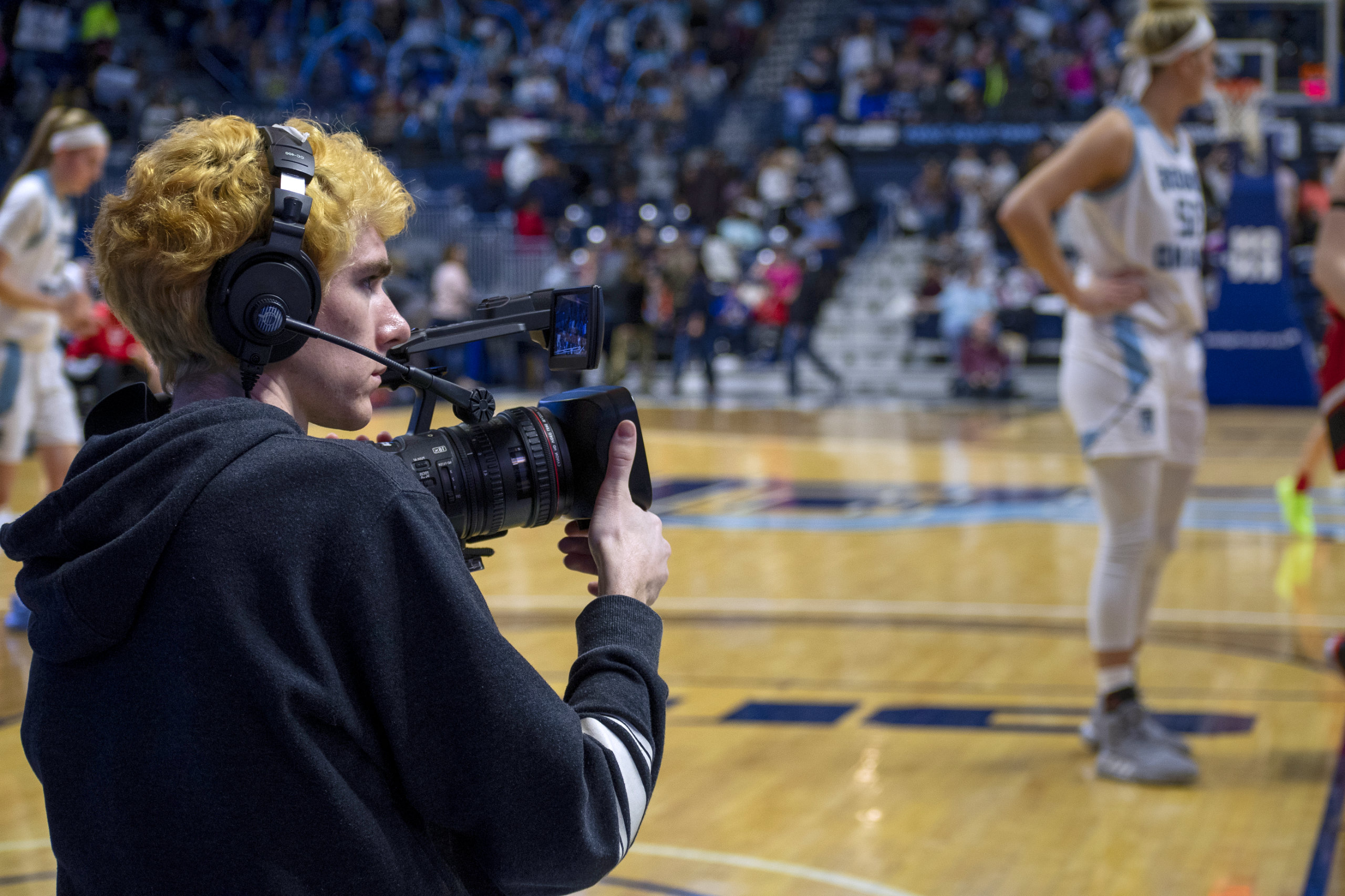 A student with video equipment films a basketball game.