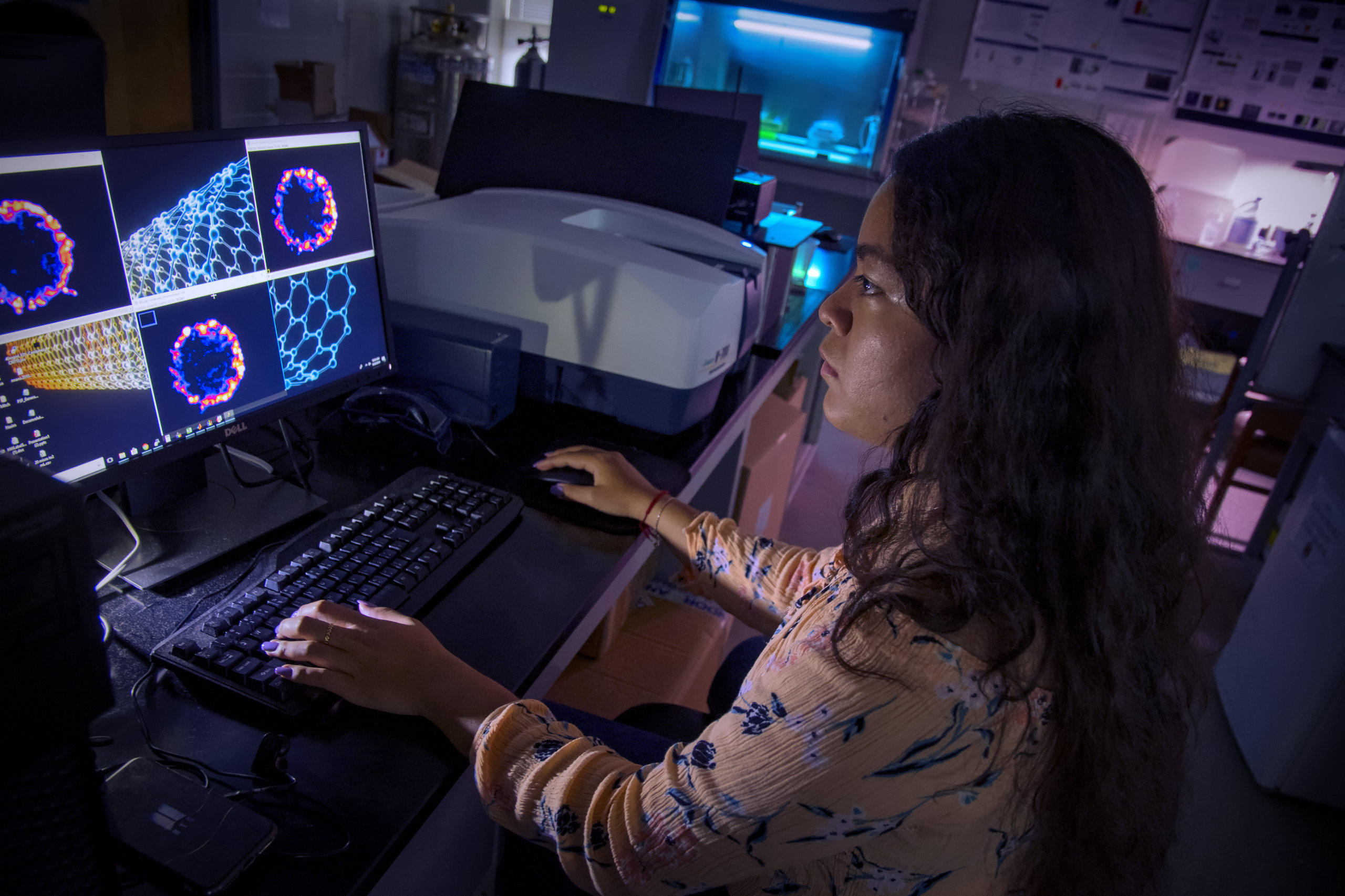A researcher looks at molecules on a computer screen in a lab.