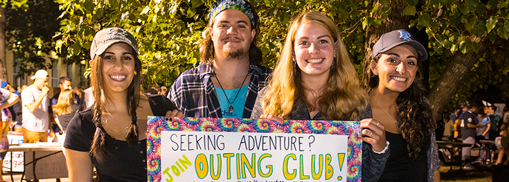 Students holding a poster for the Outing Club