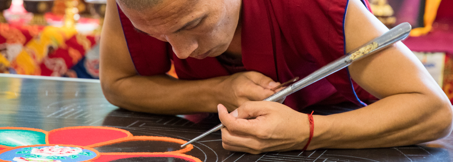A Tibetan Buddhist monk from the Drepung Loseling Monastery works on a mandala of compassion in the University of Rhode Island's Memorial Union