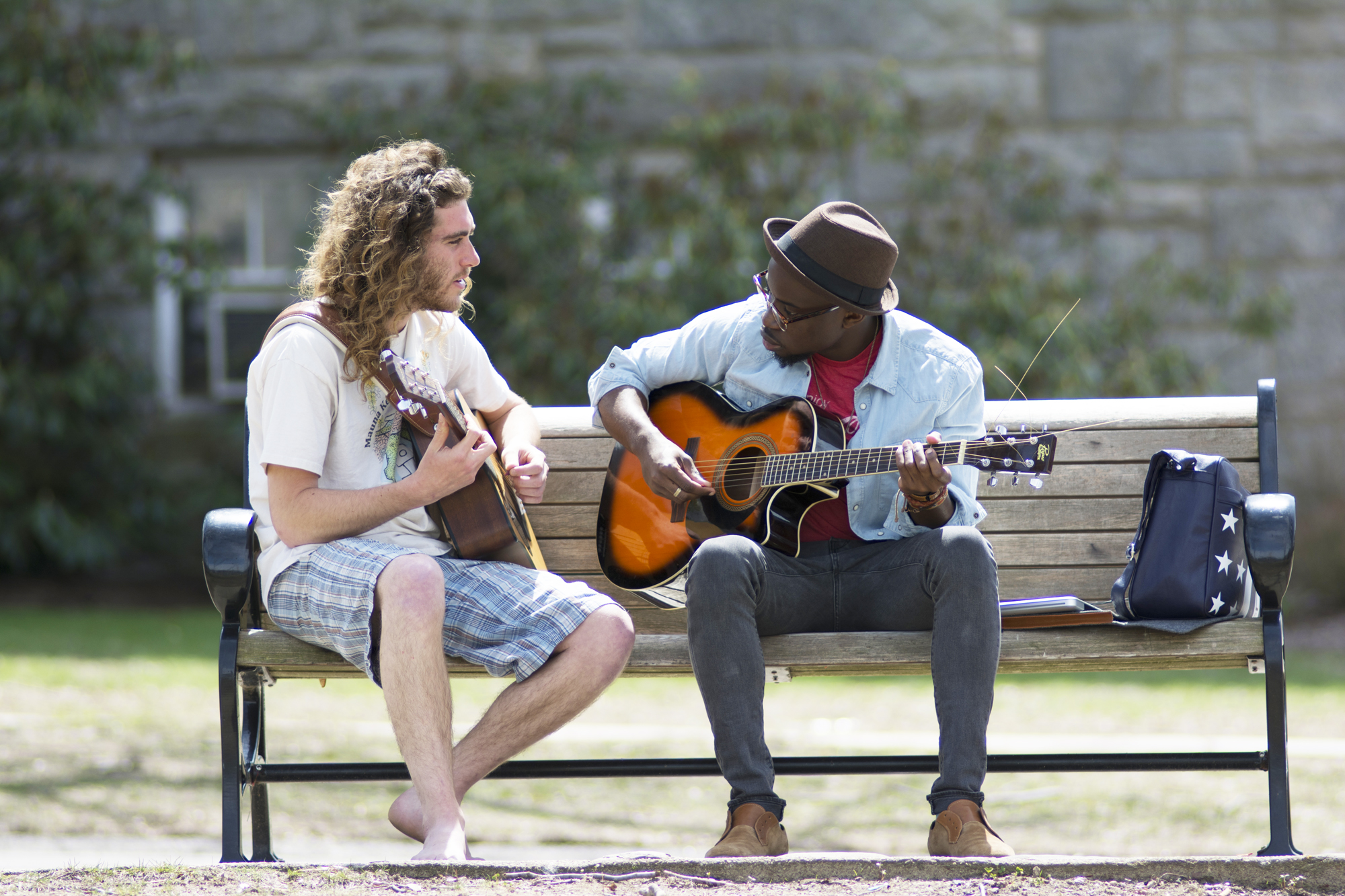 students playing guitar on a park bench