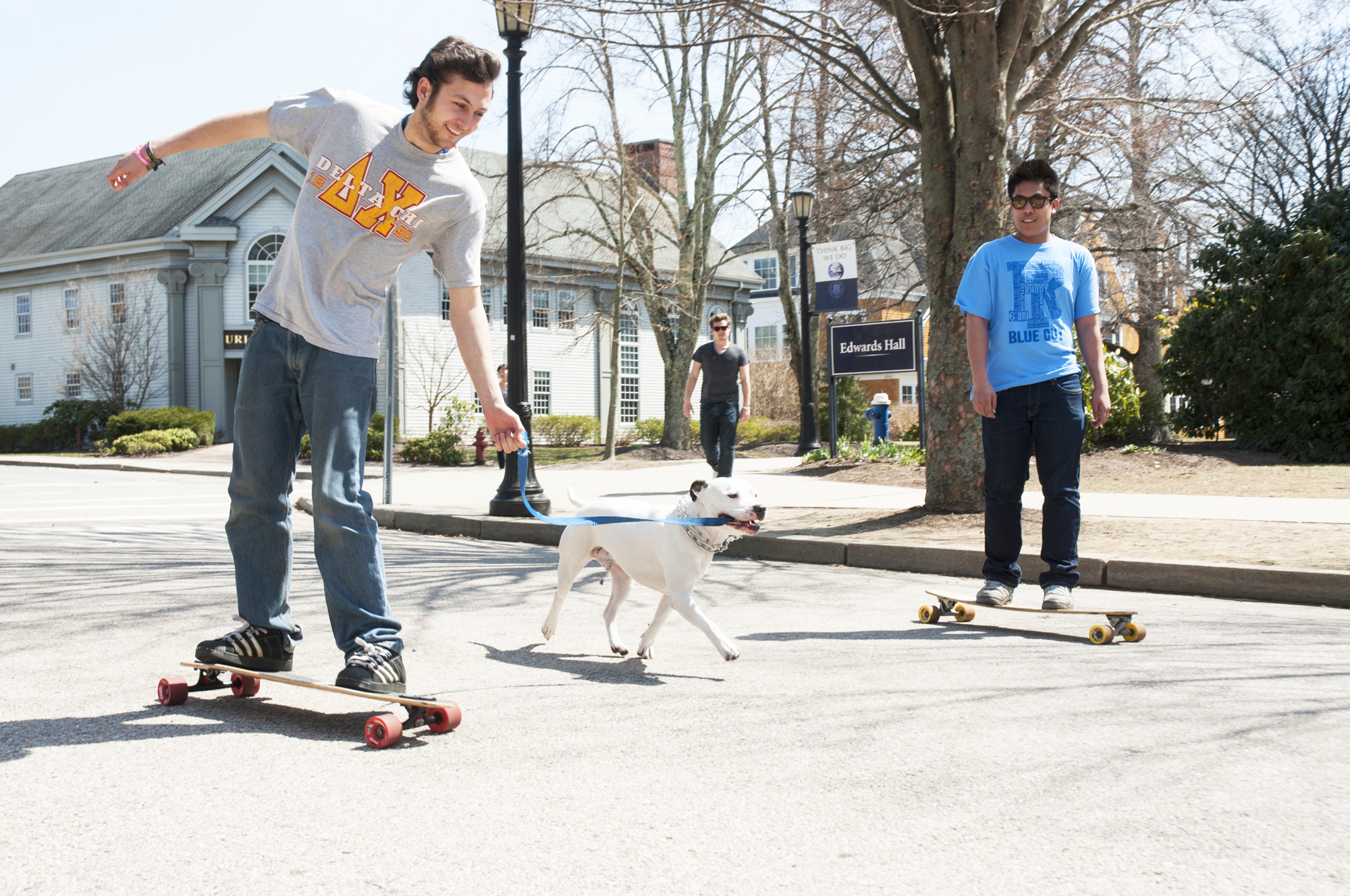 two students long boarding with a dog