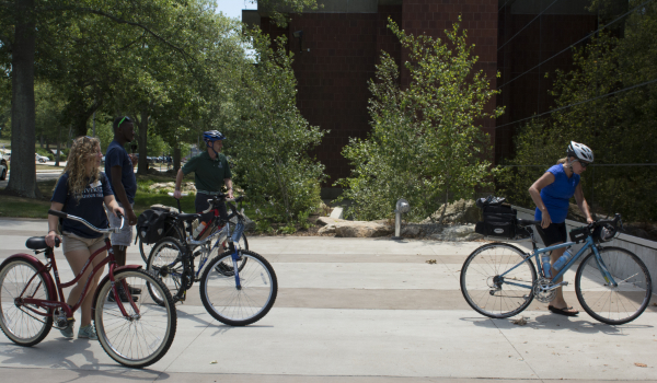 A group of counselors on riding on campus on their bikes.