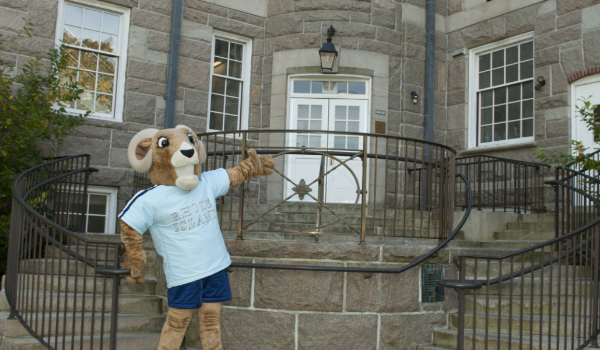 Rhody the ram standing in front of Green Hall to welcome visitors.