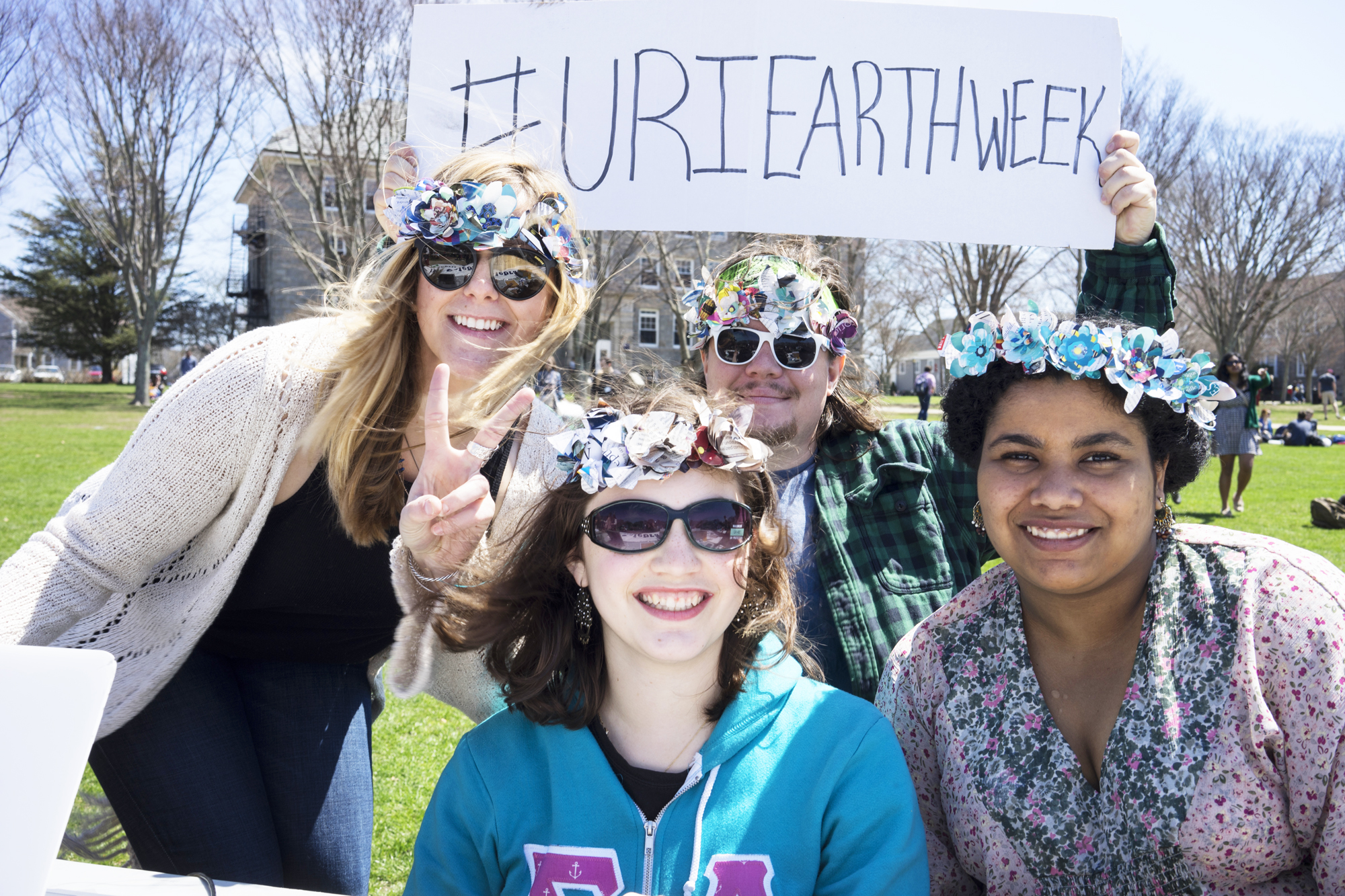 students on the quad holding #URIEarthWeek sign
