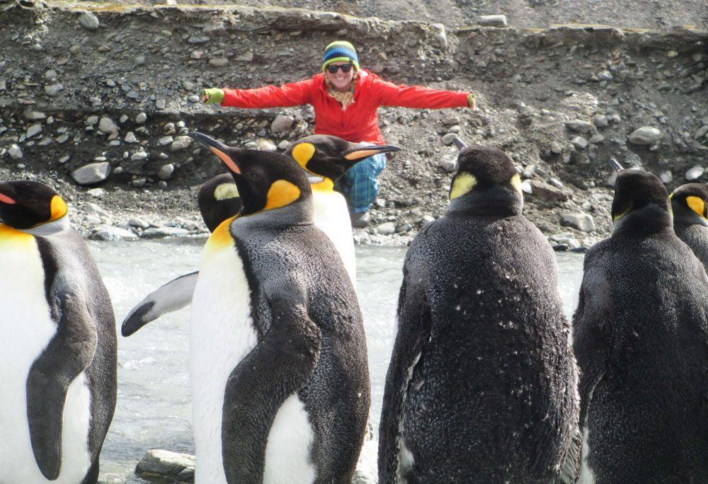 Breezy Grenier with penquins, St. Andrews Bay, Antarctica.