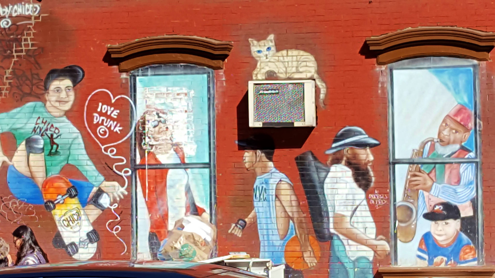 Red brick building with painted images of people in the neighborhood