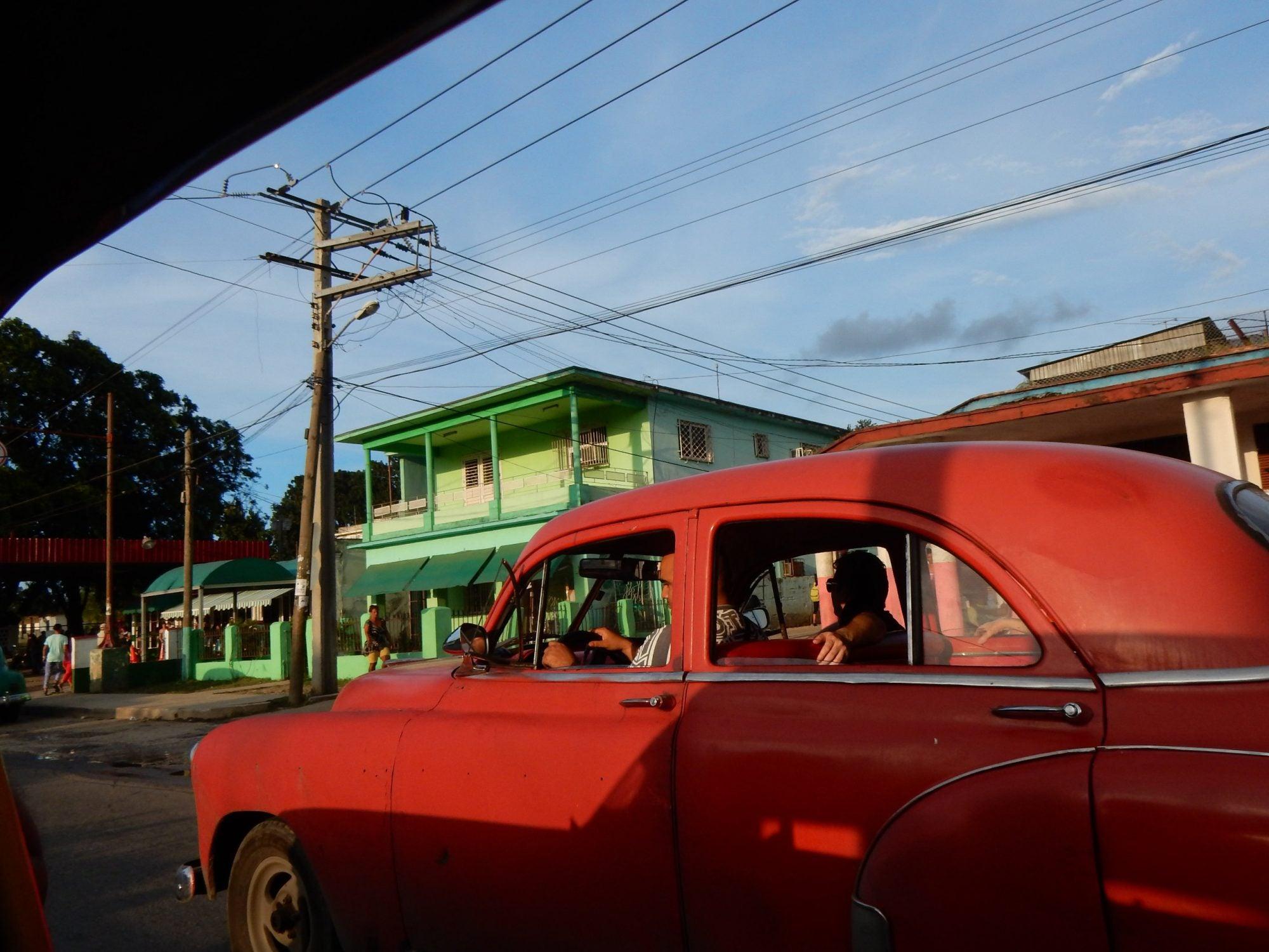 A classic car drives through Cuba