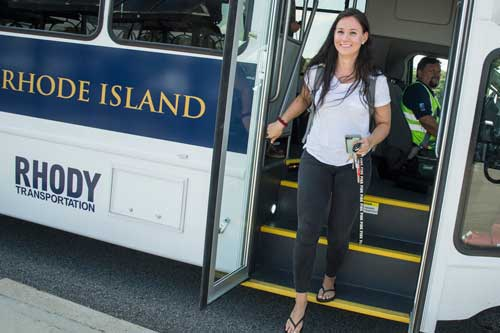 student stepping off one of the new Rhody shuttles