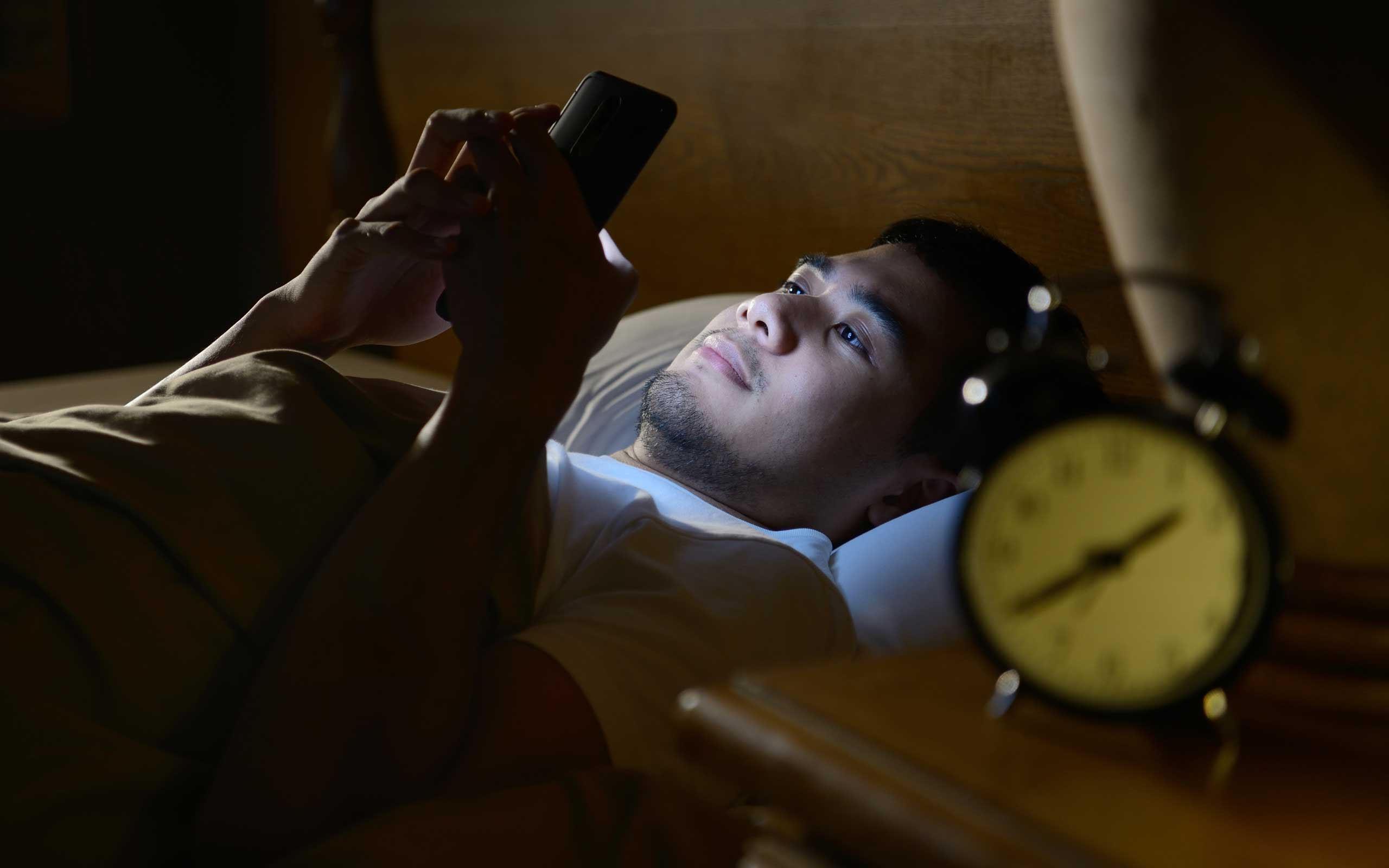 Student wide awake in bed at night texting