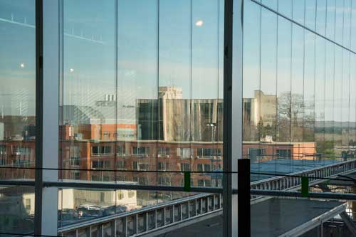 campus reflected in glass walls of new engineering complex