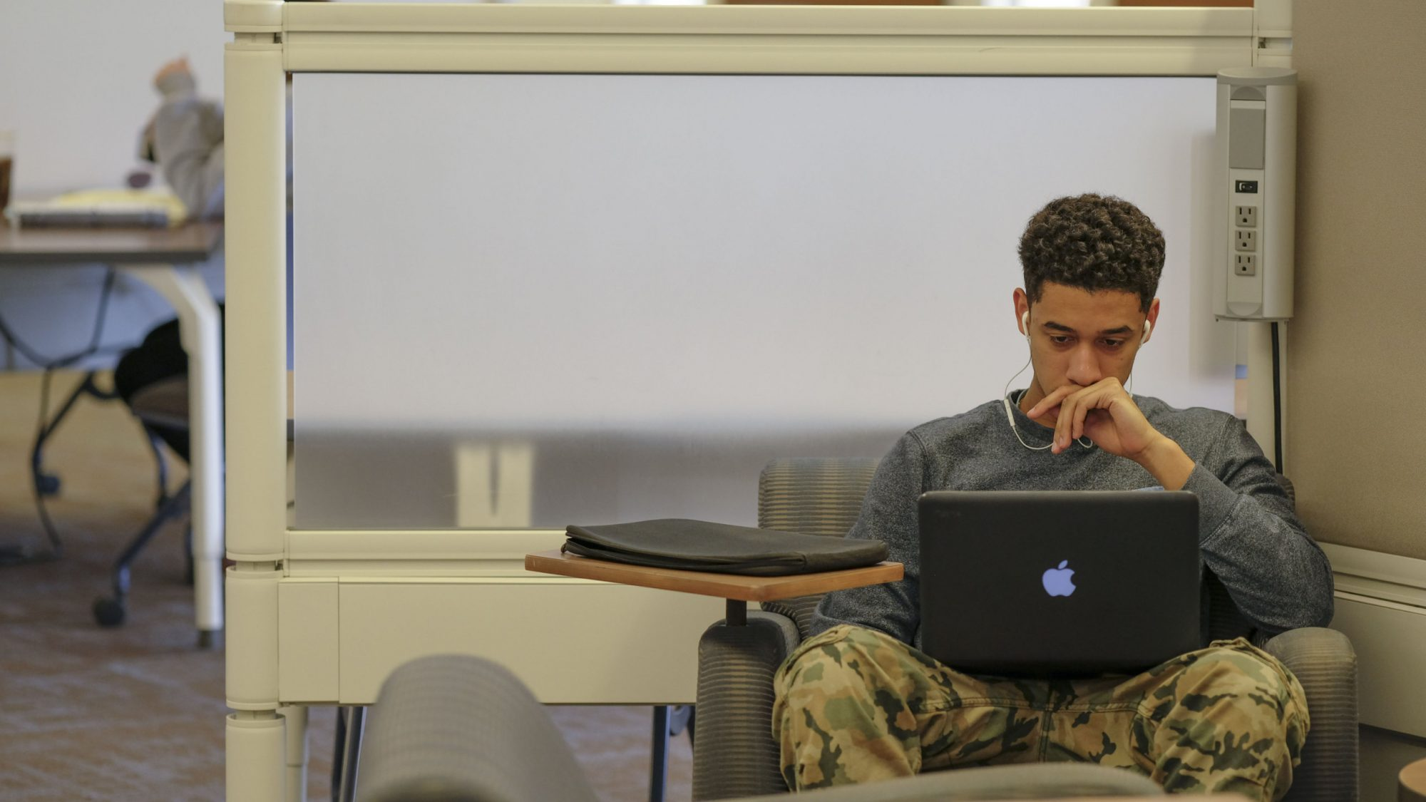 A student sits in the library looking at a laptop