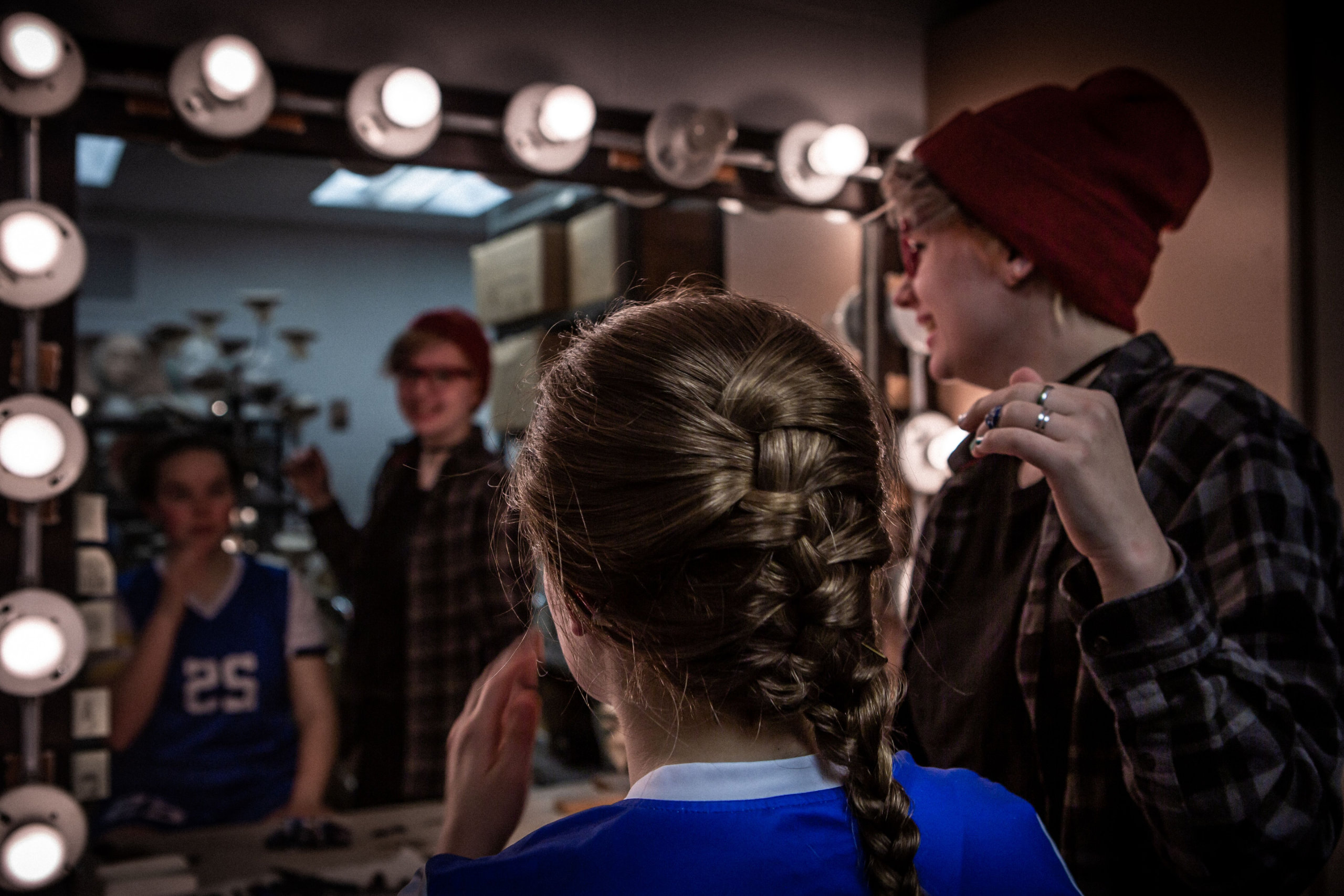 Athena Nakrosis affixes actor Madison Cook-Hines' wig backstage