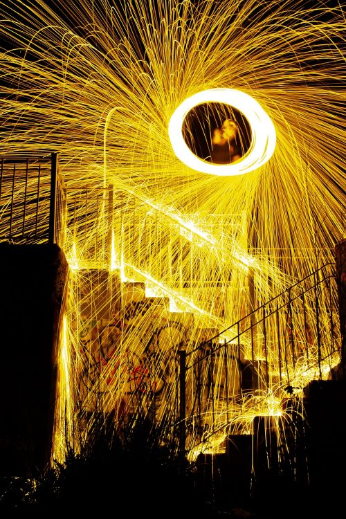 long-exposure photograph of burning steel wool being spun on a rope