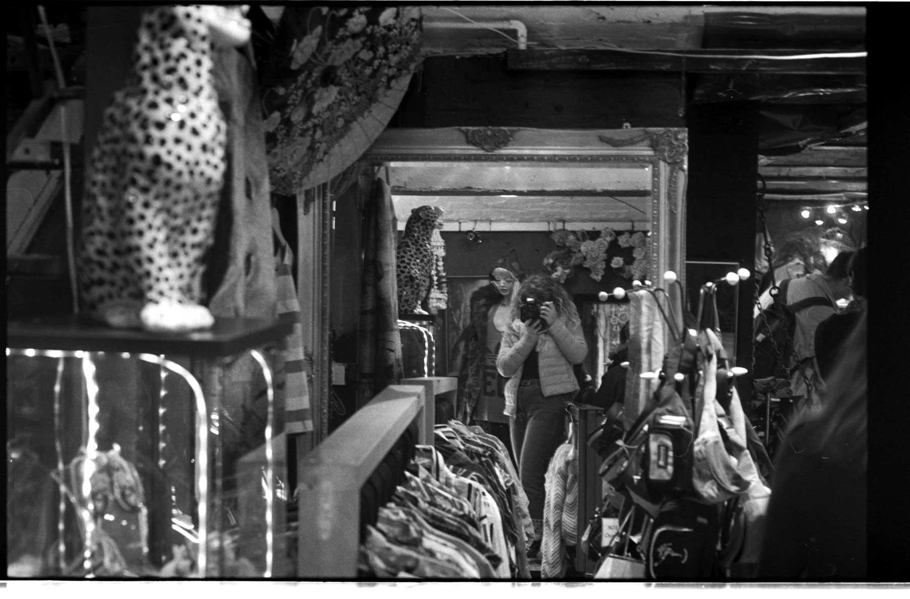 Reflection of a photographer taking a shot of crowded shop