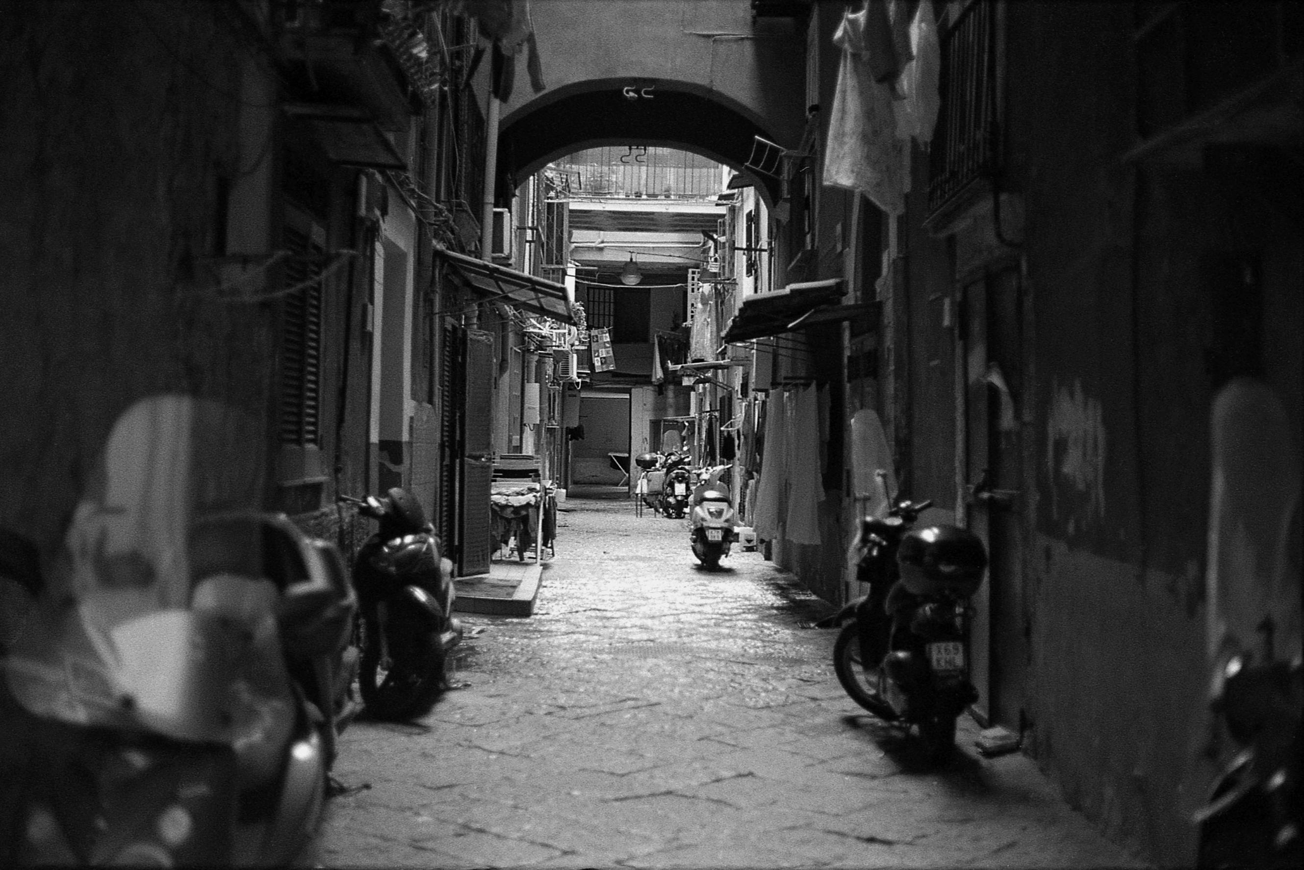 Looking down an narrow alley with motorcycles outside the doorways