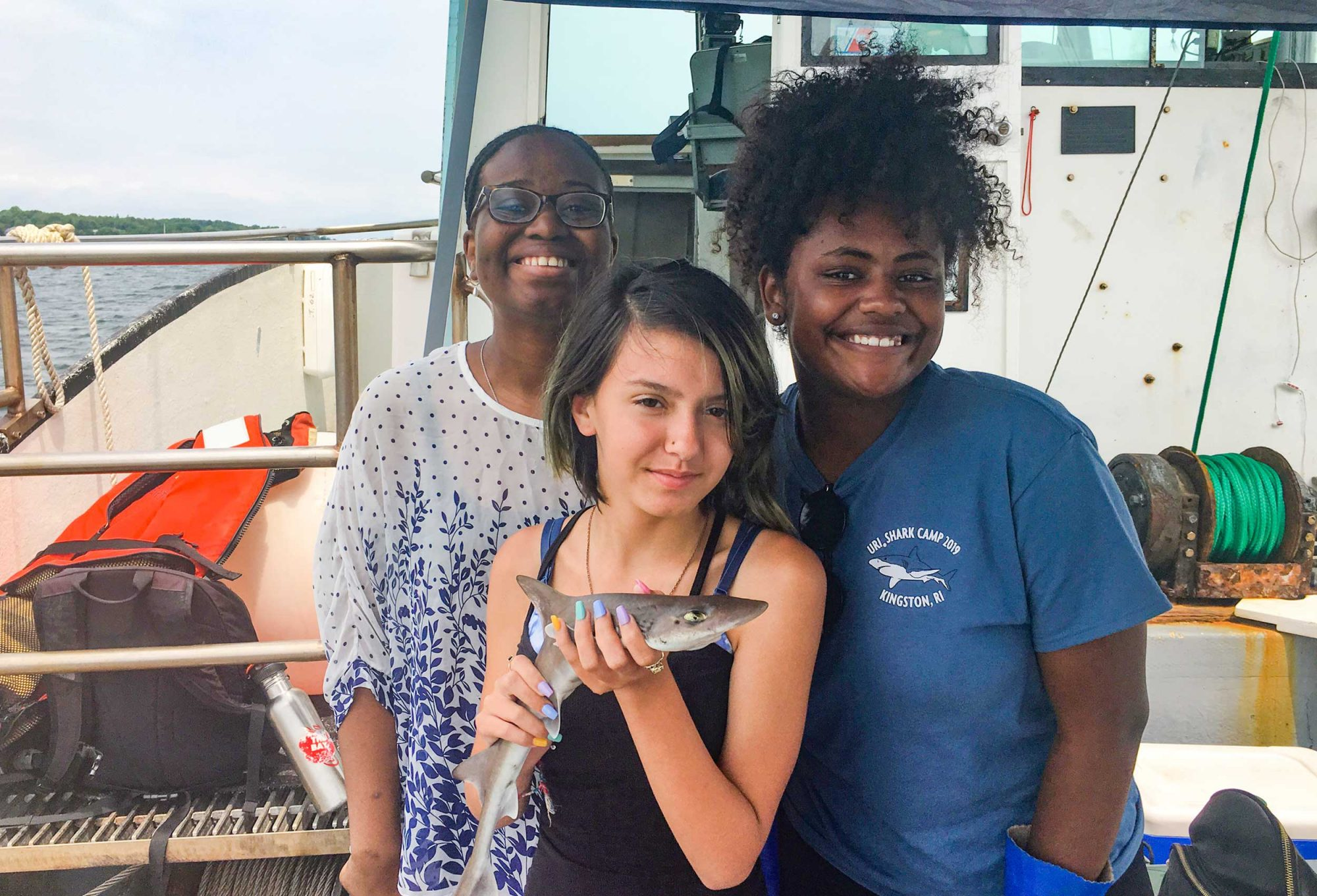 Two URI Shark Camp undergraduate researchers along with a high school student holding a shark