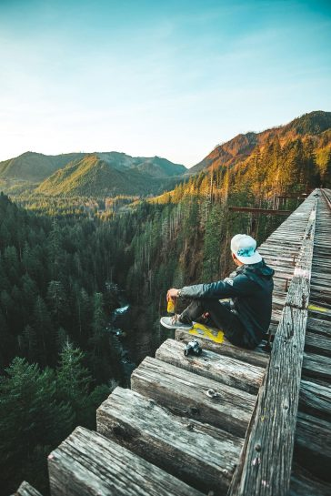 Corey Favino sitting on an old elevated railroad bridge in Washington state