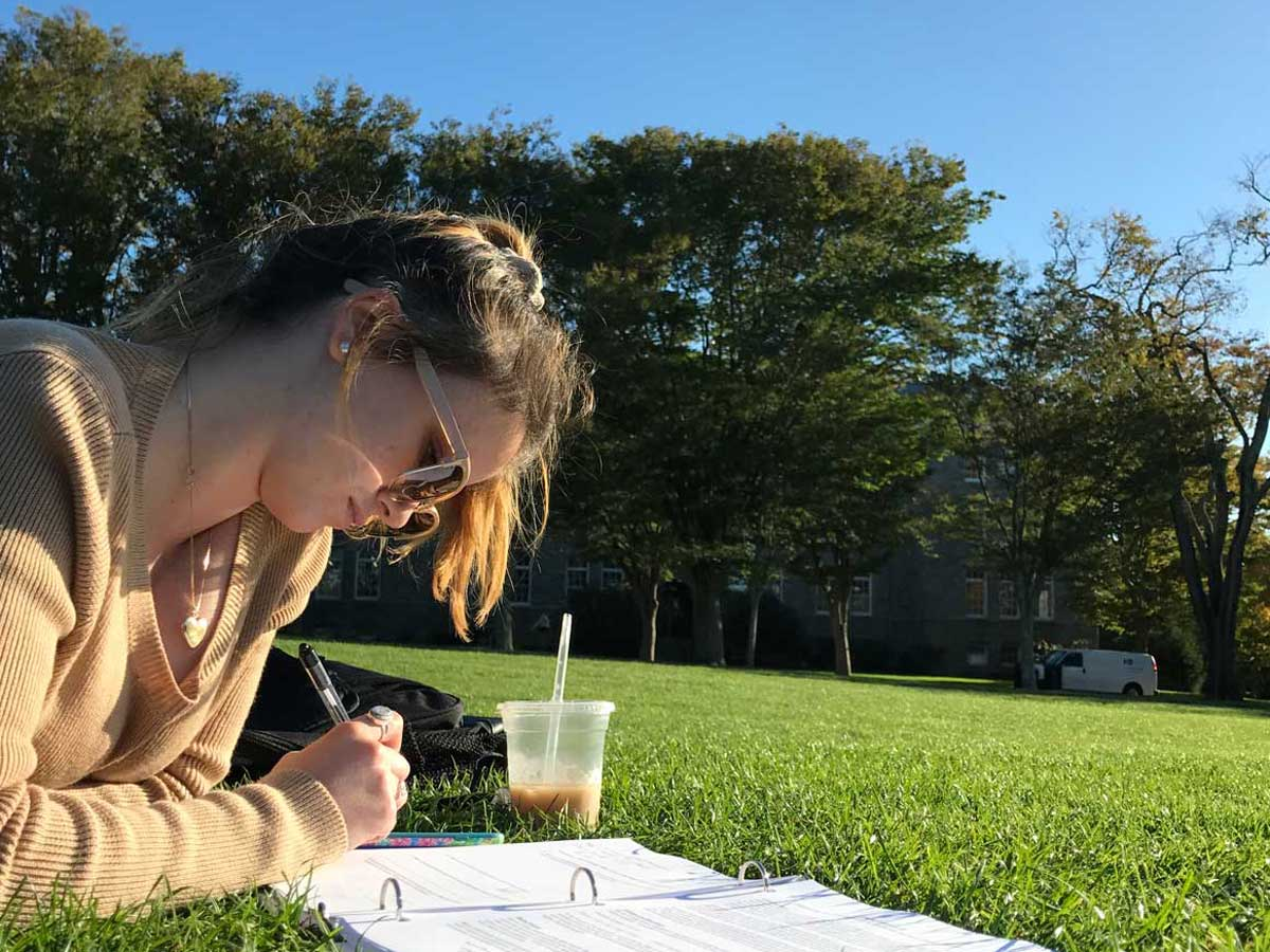 Girl writing in a notebook on the Quad