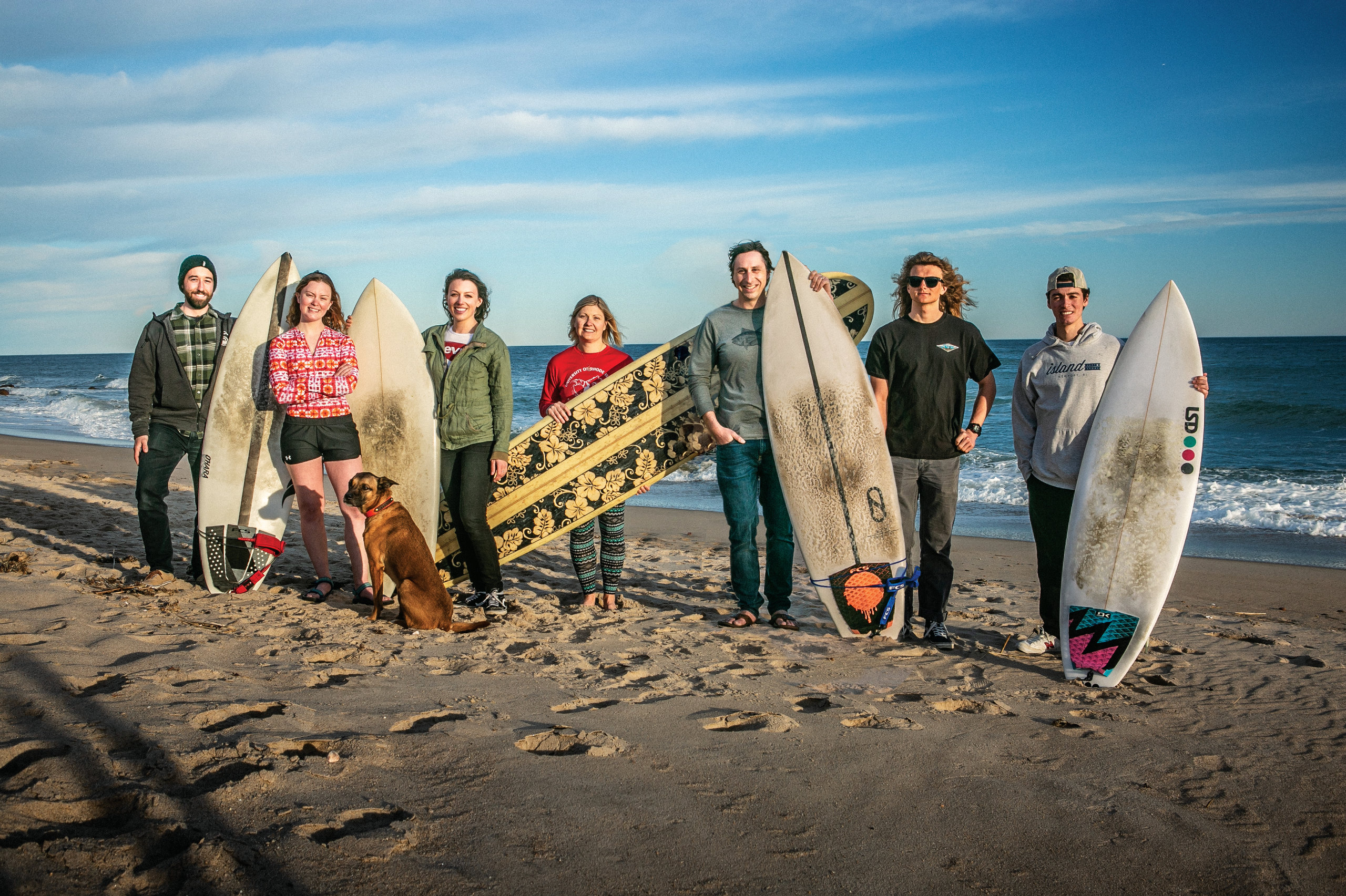 URI faculty and students stand with their surfboards on the beach