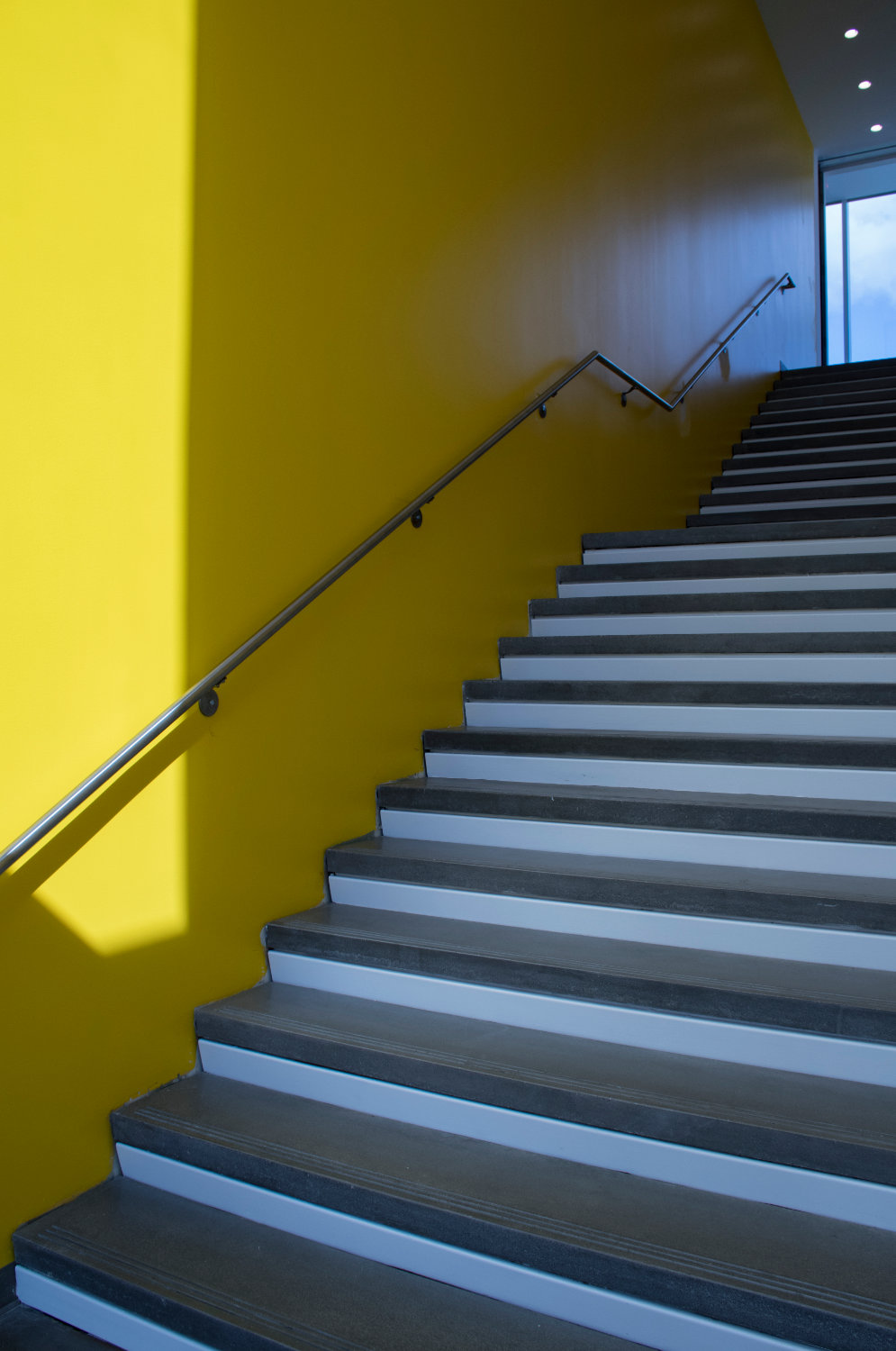 A staircase accented by a vivid yellow wall.