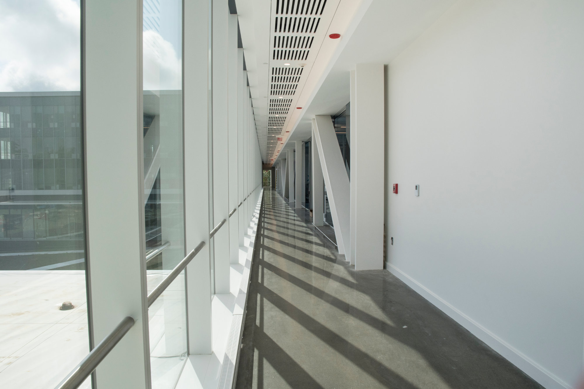 A bright open corridor on the fourth floor shows the building's metal truss support system.